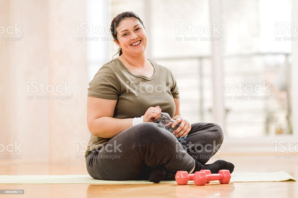 Overweight woman taking a break from exercising. stock photo