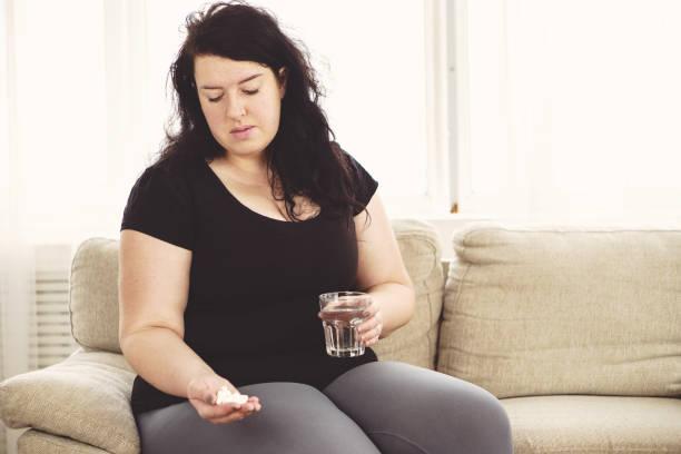 overweight woman taking pills. weight loss stock photo