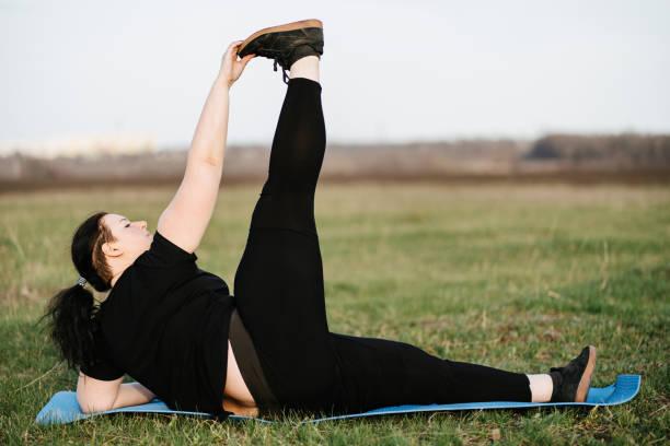 Overweight woman training legs on yoga mat outdoor stock photo