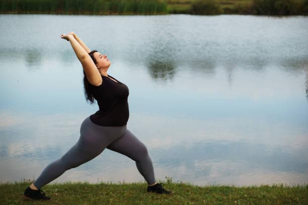übergewichtige frau, die ausbildung in der nähe von see - damen sporthose übergröße stock-fotos und bilder