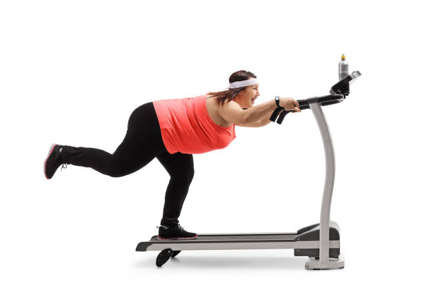 overweight woman trying not to fall off a treadmill - funny fat lady stock photos and pictures