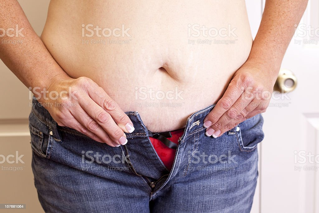 Overweight woman trying to button her jeans. Too tight. Belly. stock photo
