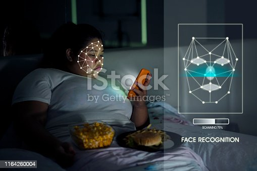 istock Overweight woman using Face ID recognition 1164260004