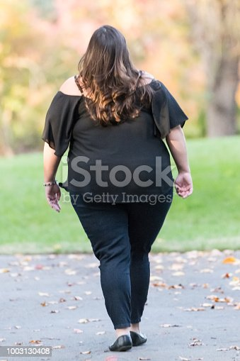 Overweight woman walking from behind in a park
