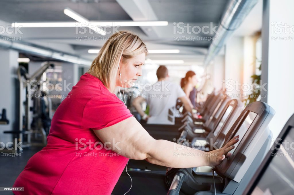 Overweight woman walking on treadmill in modern gym. stock photo