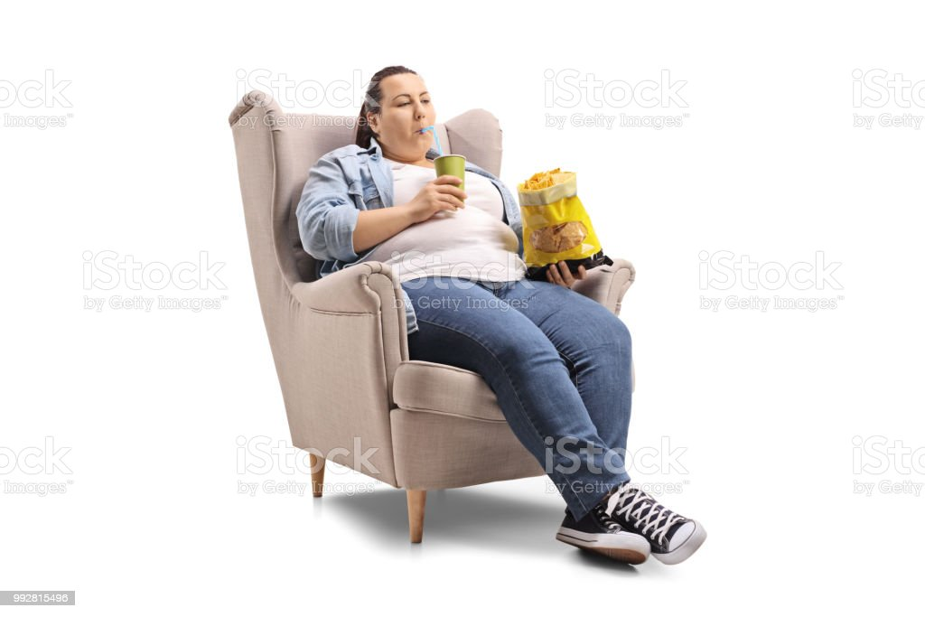 Overweight woman with a drink and a bag of chips sitting in an armchair stock photo
