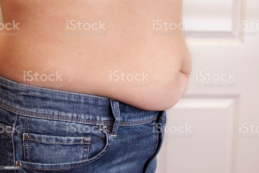 Overweight woman with belly hanging over jeans. royalty-free stock photo