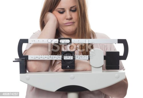 Sad and worried woman on a medical weight scale. white background.