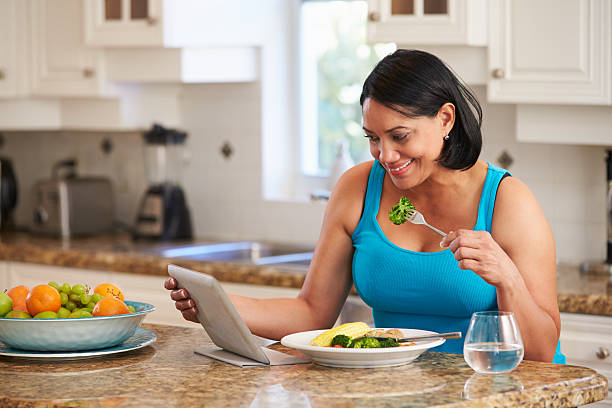 overweight woman with digital tablet checking calorie intake - fat nutrient stock photos and pictures