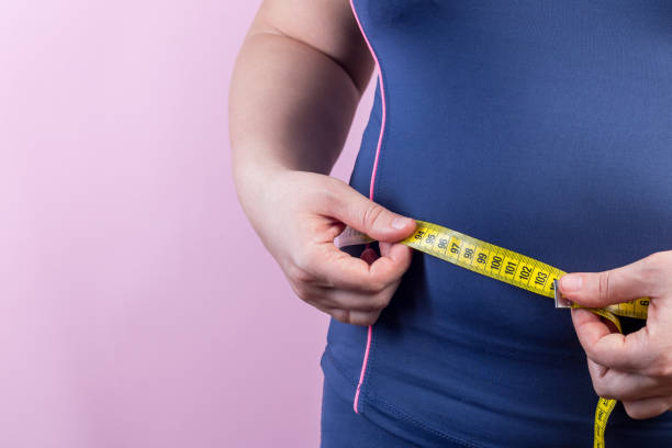 Overweight woman with measuring tape on waistline, closeup stock photo