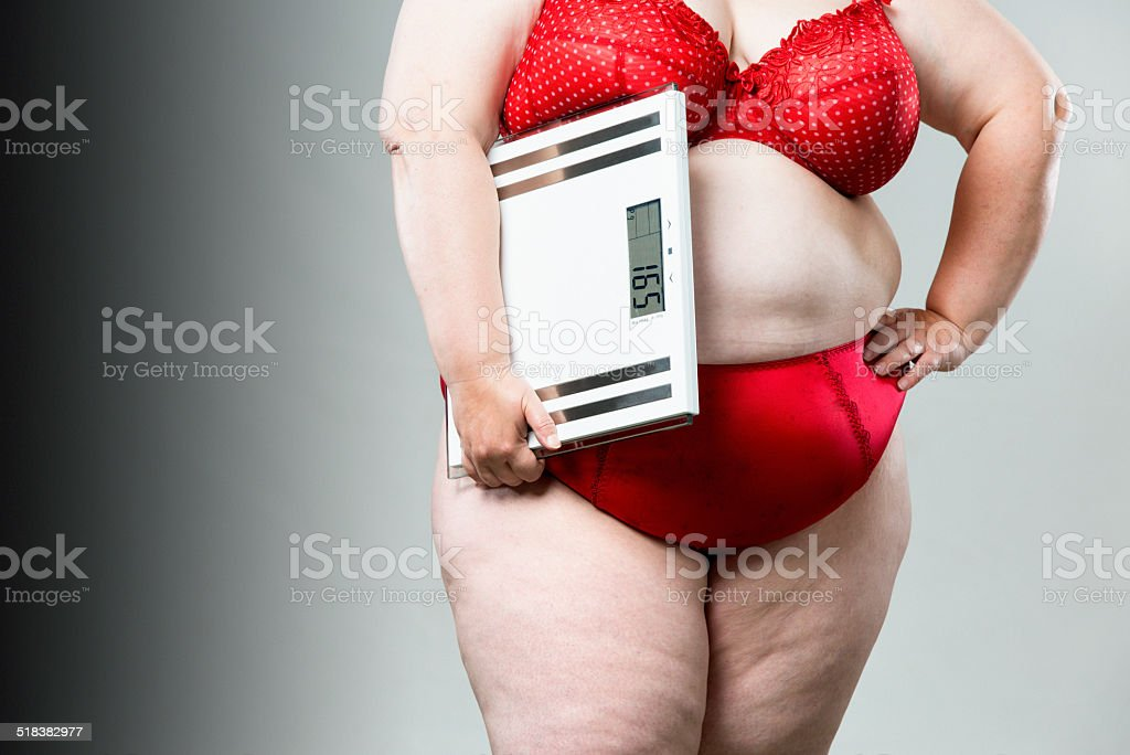 Overweight woman with scales stock photo