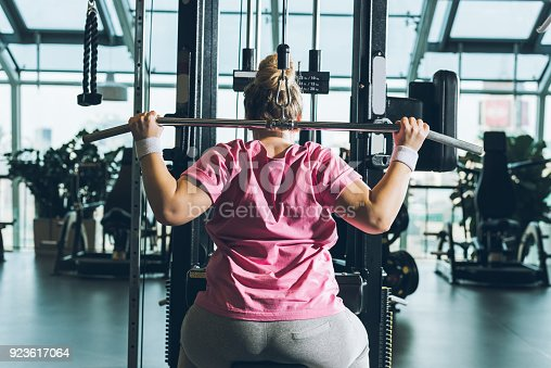 istock overweight woman working out on training apparatus 923617064
