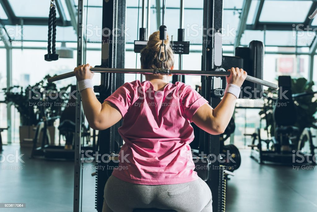 overweight woman working out on training apparatus stock photo