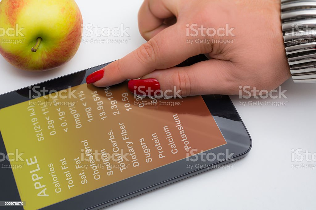 Overweight woman's hand checking the calories of an apple stock photo
