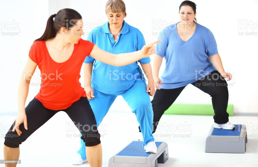 Overweight women exercising with instructor. stock photo
