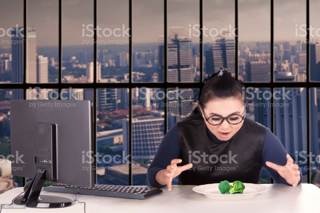 Overweight worker wants to eat broccoli stock photo