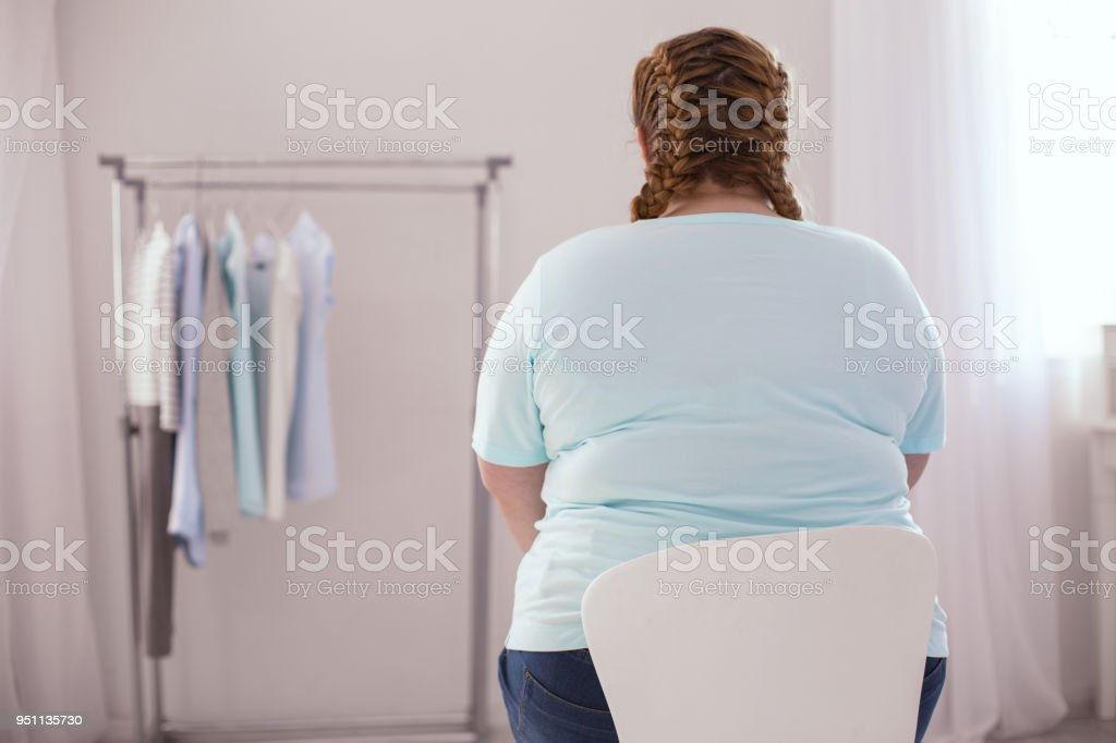 Übergewichtige junge Frau sitzt auf dem Stuhl – Foto