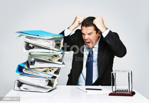 istock Overwhelmed businessman furious at pile of work 169941027