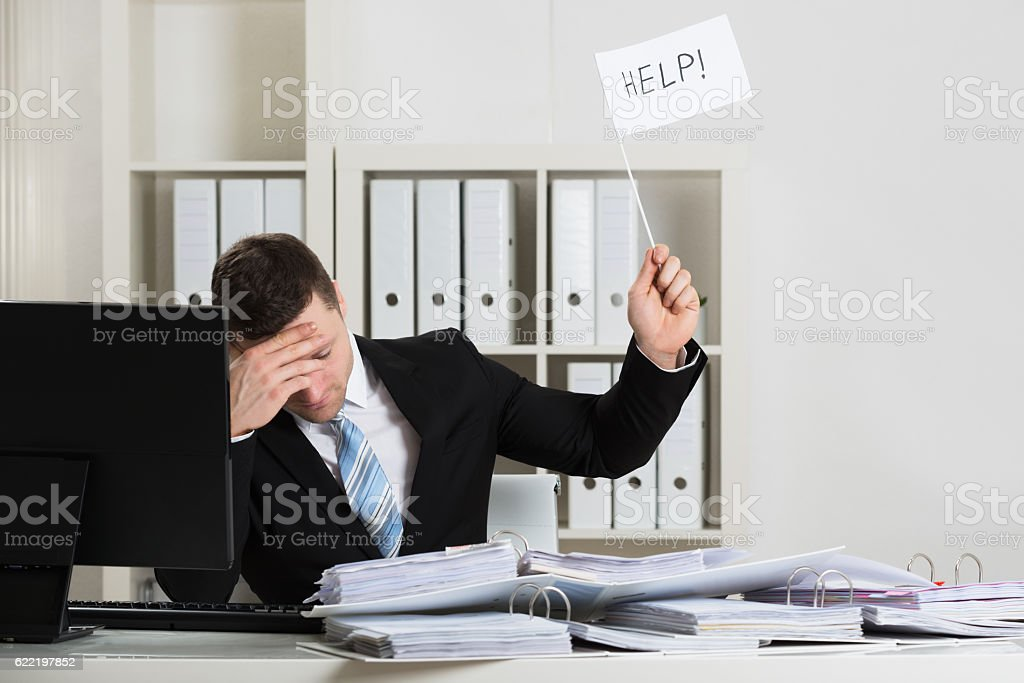 Overworked Accountant Holding Help Sign At Desk stock photo