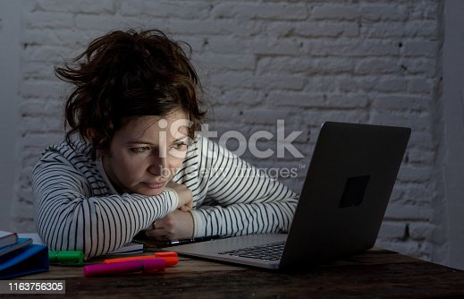 istock Overworked and tired female student working late at night on laptop trying not to fall asleep and making an effort to concentrate and keep on studying. Online University and internet learning concept. 1163756305