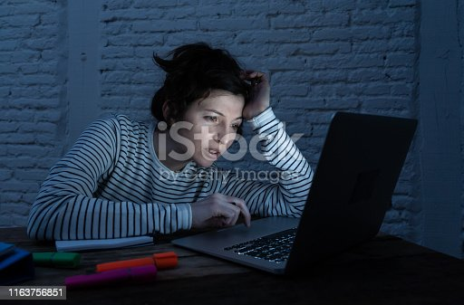 istock Overworked and tired female student working late at night on laptop trying not to fall asleep and making an effort to concentrate and keep on studying. Online University and internet learning concept. 1163756851