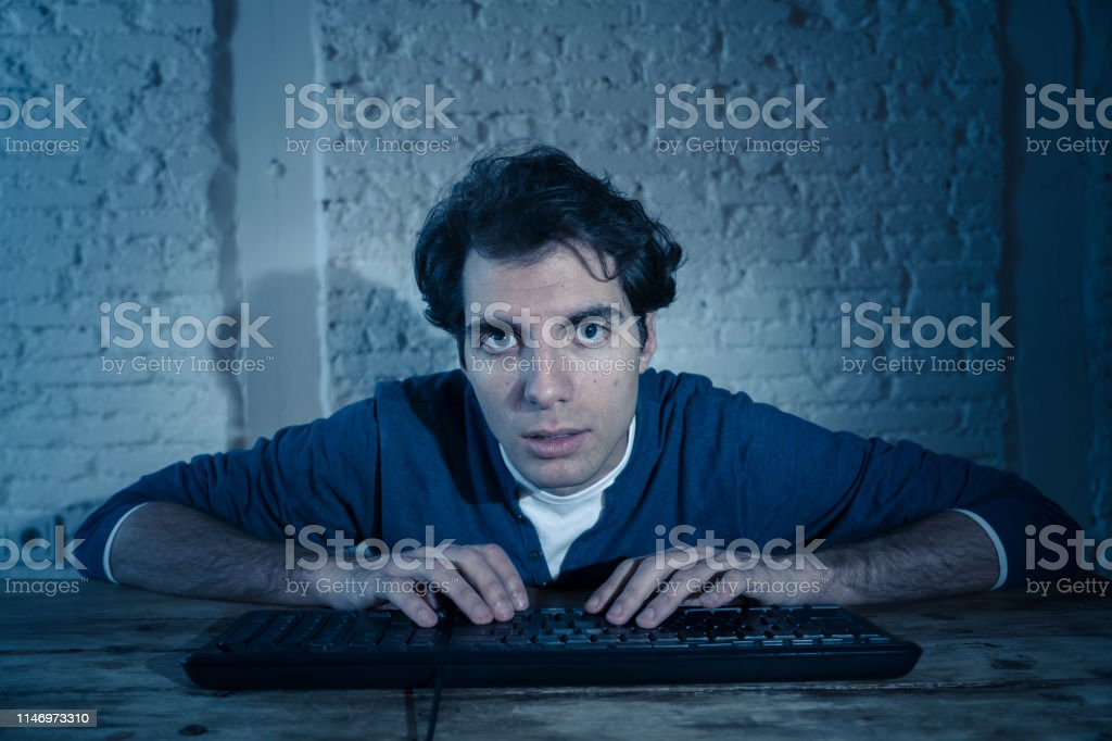 Overworked and tired male working late at night on computer trying...