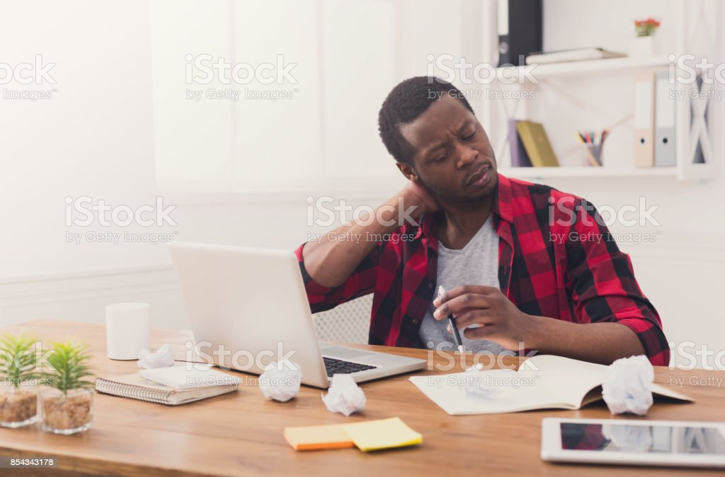 Overworked black businessman in casual office, work with laptop stock photo