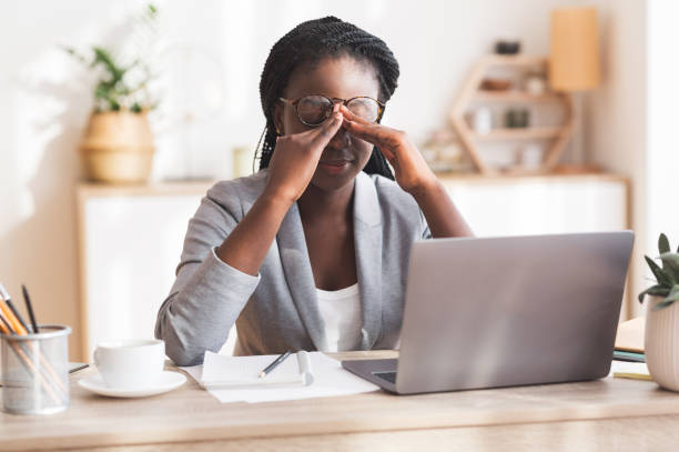 überarbeitete schwarze geschäftsfrau massaging nosebridge am arbeitsplatz mit sehproblem - frustration stock-fotos und bilder