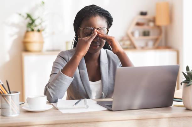 Überarbeitete schwarze Geschäftsfrau Massaging Nosebridge am Arbeitsplatz mit Sehproblem – Foto