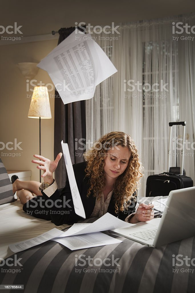Overworked Business Traveler Frustrated with Working in Hotel Room Vt royalty-free stock photo