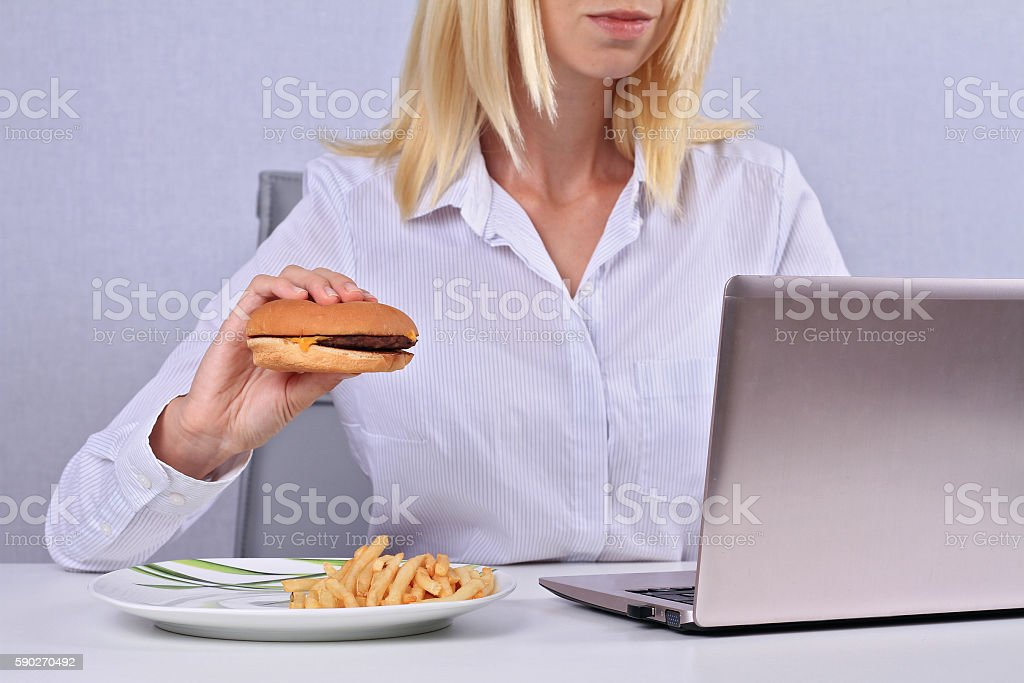 Overworked Business woman eating hamburger in an office. stock photo