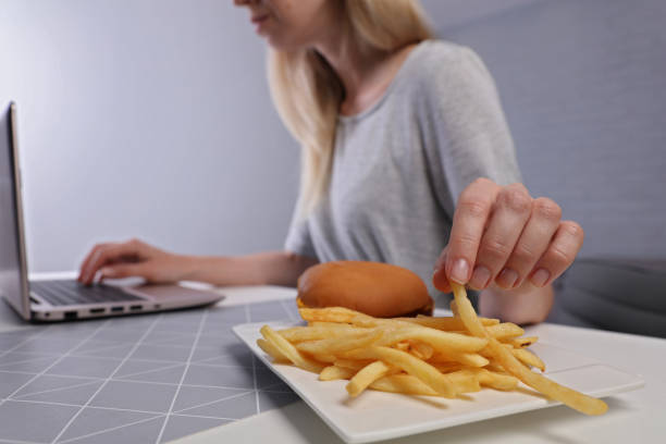 mulher de negócios sobrecarregada comendo hambúrguer / sucata de comida para o seu jantar. comer saudável leva a gastrite crônica ou úlcera - junk food - fotografias e filmes do acervo