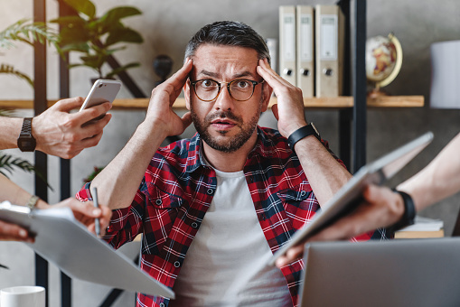 Overworked businessman sitting at laptop overloaded with work multiple tasks in modern office