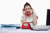 istock Overworked businesswoman answering the phones 823923960