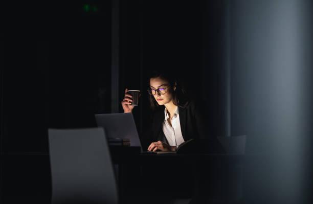 empresaria sobretrabajada trabajando tarde en la oficina - trabajar hasta tarde fotografías e imágenes de stock