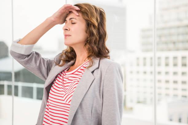 überarbeitete casual geschäftsfrau mit kopfschmerzen - migräne vorbeugen stock-fotos und bilder