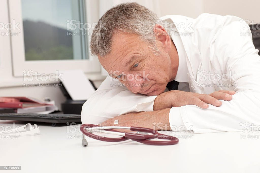 Overworked doctor having burn out stock photo