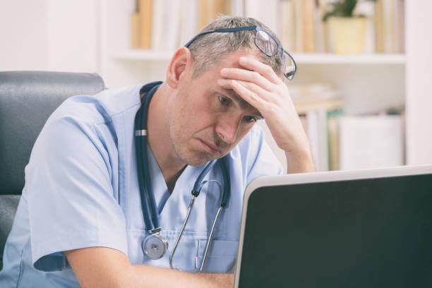 Überlasteter Arzt in seinem Büro – Foto