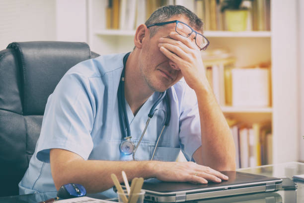 Overworked doctor in his office stock photo