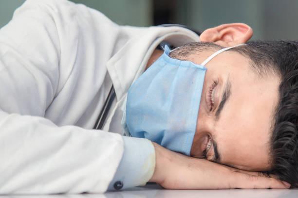 Überlasteter männlicher Arzt nappt auf Stuhl im Krankenhaus – Foto