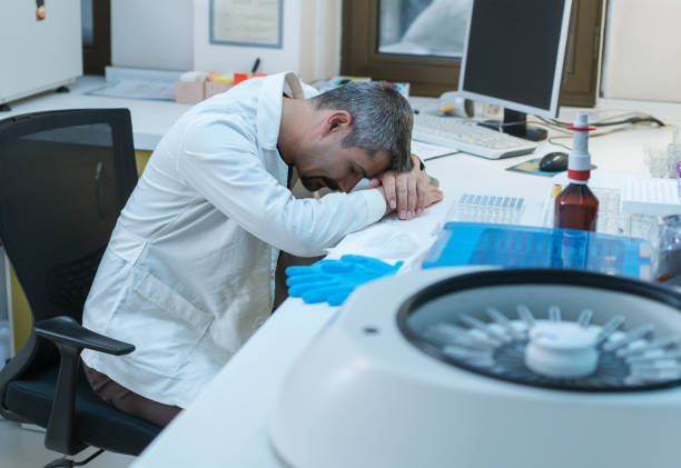Overworked male medical professional is sleeping on desk in hospital stock photo