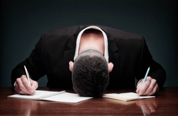 Overworked man collapses while writing stock photo