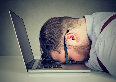 Side view of chubby man looking broken while lying on top of laptop.