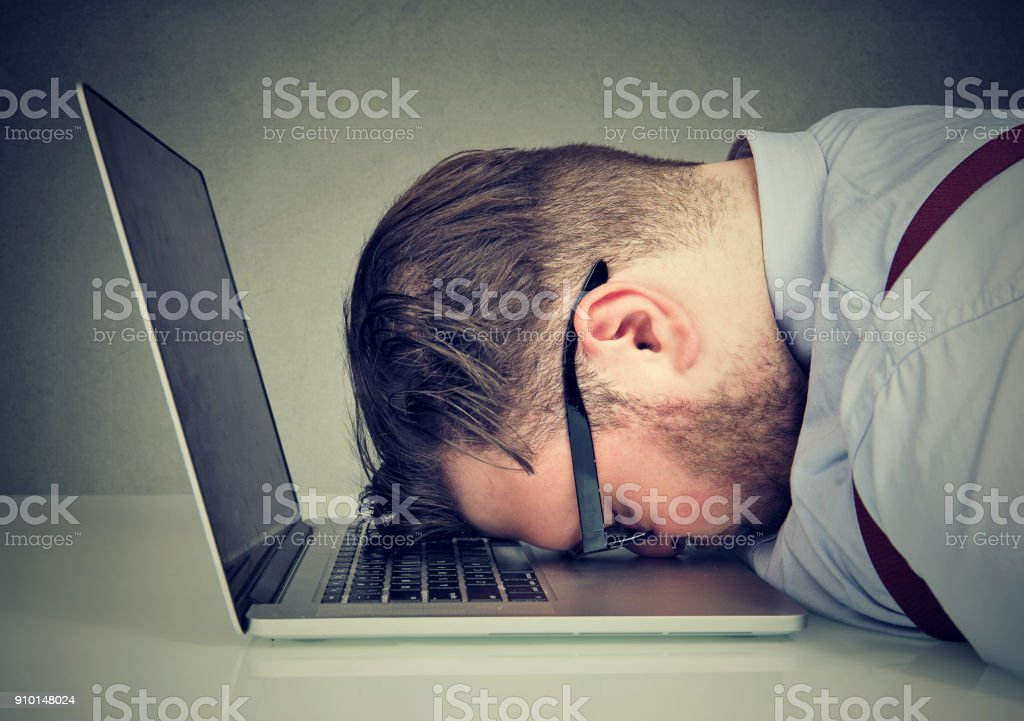 Overworked man lying on laptop stock photo