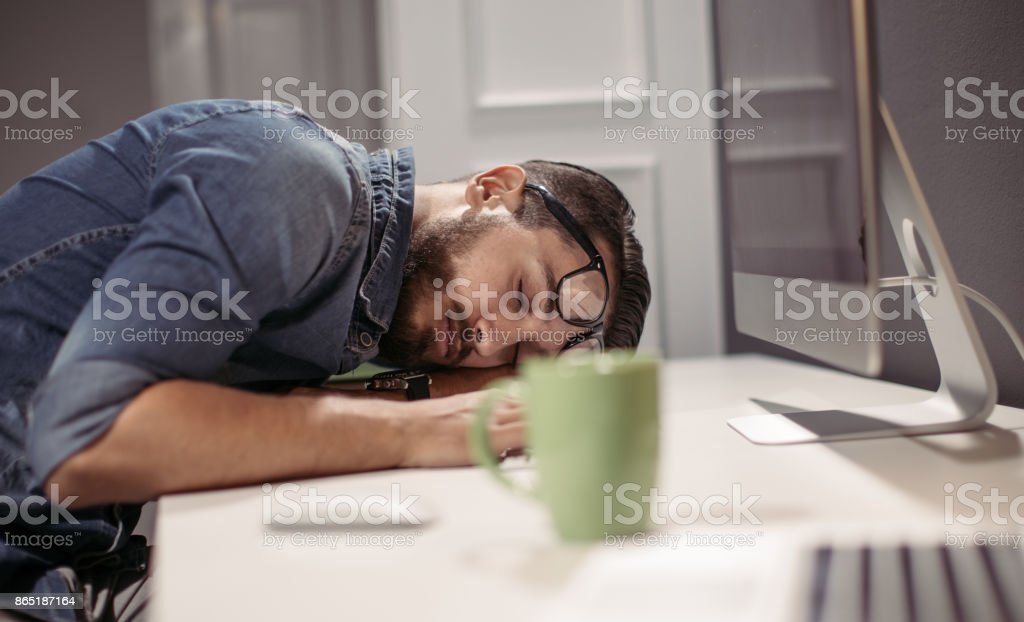 Overworked man sleeping in the office stock photo