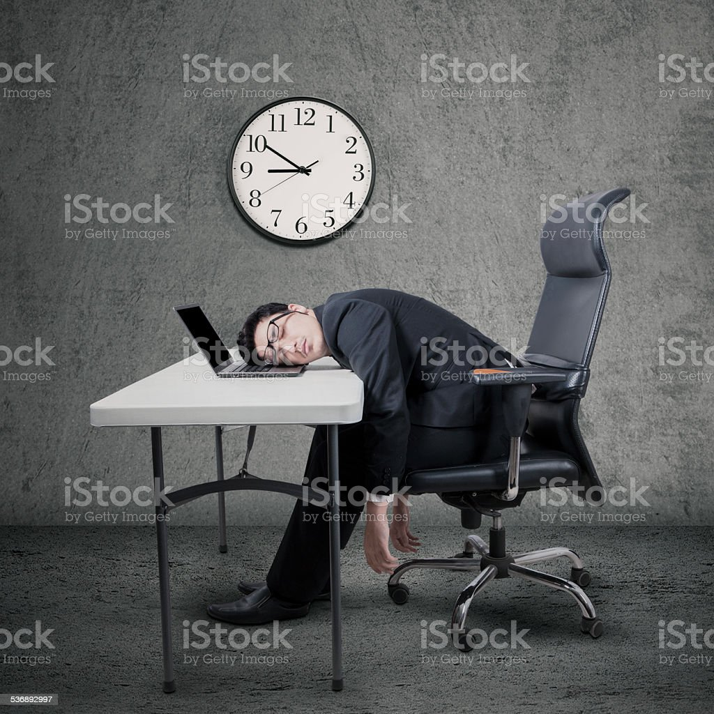 Overworked manager sleeping at desk stock photo