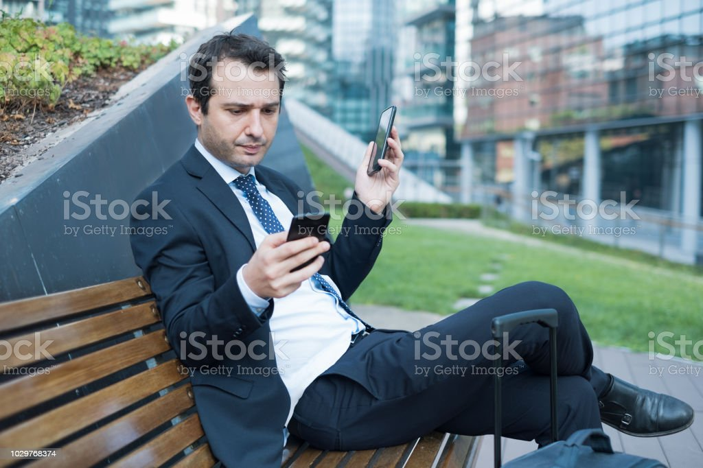 Overworked manager using two cellphones stock photo