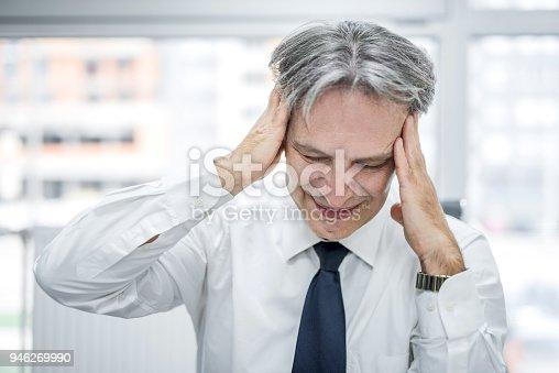 istock Overworked mature businessman having a headache. 946269990