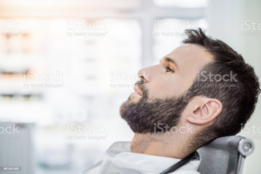 Overworked mid adult male healthcare worker having a lot going on in his mind. stock photo