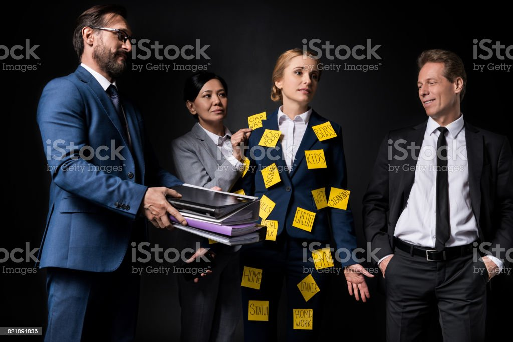 overworked middle aged businesswoman with sticky notes on clothes holding smartphone while standing with colleagues isolated on black stock photo